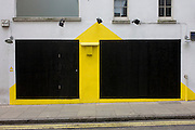 Yellow triangle on the side of a closed business in central London.