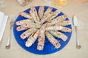 gratinated squilla mantis on blue round glass dish  with fork,fish knife,white wine, italian traditional food of Romagna,side view from above