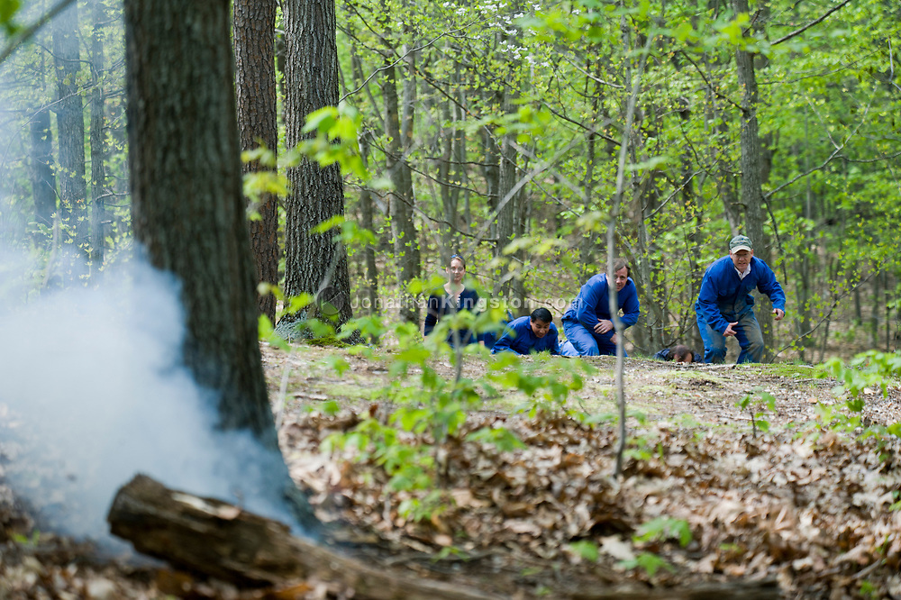 A simulated explosing rocks the Virginia woods as HEFAT students approach a simulated refugee camp where they have come to interview its inhabitants. Hostile Environments and Emeregency First Aid Training course for journalists deploying to war zones in Strausburg, VA. (Model Released)