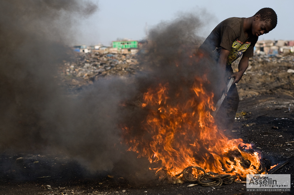 A boy stirs the fire he uses to burn plastic off computer parts to recover copper that he will then sell for money near the Agbogboloshie market in Accra, Ghana on Thursday August 21, 2008.