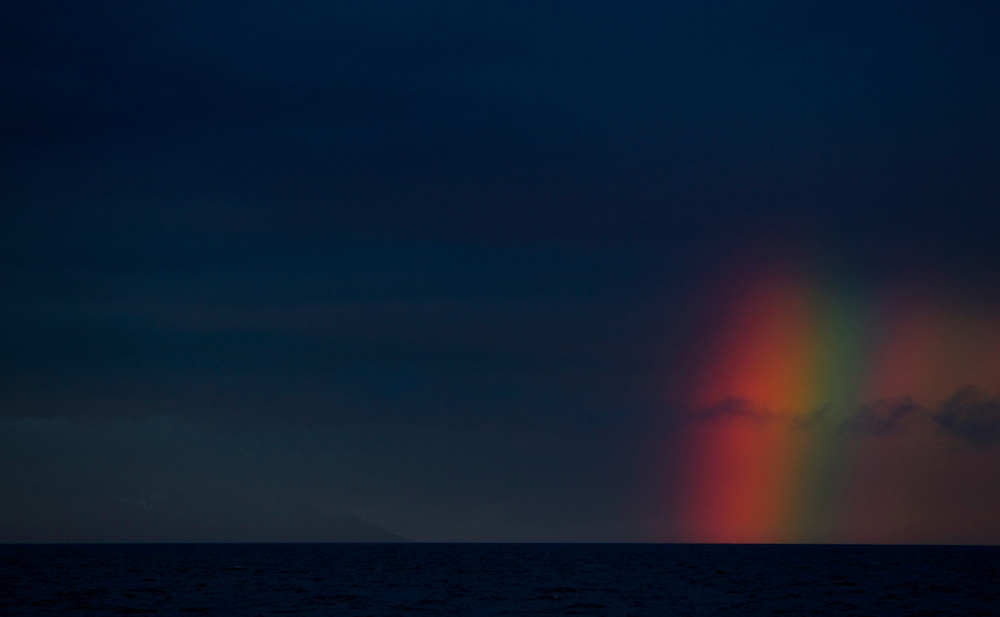 A rainbow appears on the horizon of Cooks Inlet.