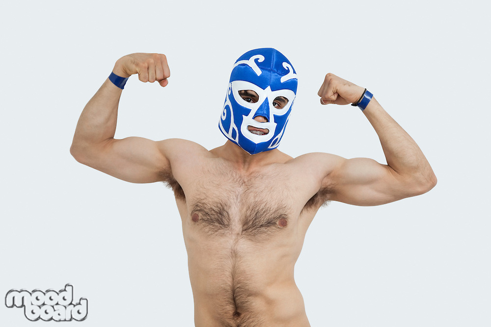 Portrait of a shirtless man in wrestling mask flexing muscles over gray background