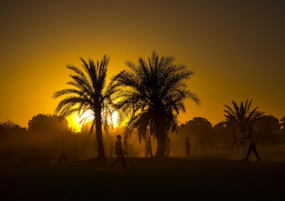Tumbus, Sudan, kids playing football in the desert at sunset.
