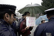 Police prepare to escort away a man standing in protest of a proposed visit to controversial Yasukuni Shrine by Japan's prime minister in Tokyo, Japan. very year on August 15, the day Japan officially surrendered in WWII, tens of thousands of Japanese visit the controversial shrine to pay their respects to the 2.46 million war dead enshrined there, the majority of which are soldiers and others killed in WWII and including 14 Class A convicted war criminals, such as Japan's war-time prime minister Hideki Tojo. Each year speculation escalates as to whether the country's political leaders will visit the shrine, the last to do so being Junichiro Koizumi in 2005. Nationalism in Japan is reportedly on the rise, while sentiment against the nation by countries that suffered from Japan's wartime brutality, such as China, has been further aggravated by Japan's insistence on glossing over its wartime atrocities in school text books...Photographer:Robert Gilhooly..