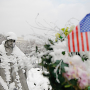 "The Korean War Memorial on the National Mall on a snowy winter morning. In the foreground at right is a commemorative wreath with an American flag. The Korean War Veterans Memorial, unveiled in 1992, sits on the northwestern end of the National Mall, not far from the Lincoln Memorial. It consists of several elements designed by different people and groups. It has a triangular footprint with the main elements being ""The Column"" consisting of 19 stainless steel solders, each over 7 feet tall, and a reflective granite wall etched with the faces of thousands of Americans who lost their lives in the war. At one end of the triangle, behind the soldiers, is a grove of trees. At the other is a large American flag and a small Pool of Remembrance. Among the designers were Frank Gaylord (the soldiers) and Louis Nelson (the reflecting granite wall)."