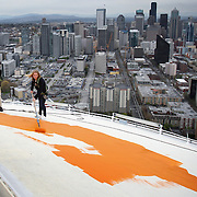 "April 17, 2012 ? Jeff Wright and his daughter Mauren Wright, 15, begin painting the roof of the Space Needle its original ""Galaxy Gold."" Jeff Wright's father Howard S. Wright built the Space Needle for the Worlds Fair. In 2012 the icon was returned to its original color as part of the celebration of the 50th anniversary of the Needle and the Seattle Center."