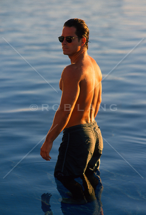 Man in sunglasses and no shirt standing in still water during a sunset
