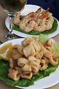 A plate of deep fried Calamari and a plate of Shrimps with sesame seed