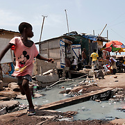 A child runs across a makeshift bridge in Old Fadama. Located in Ghana's capital Accra and colloquially referred to as 'Sodom and Gomorrah', Old Fadama is Ghana's largest slum and is home to some 80 000 people. With no public sanitation services at all, what limited toilet facilities exist in the community are privately owned and operate on a pay-per-use basis. People who cannot pay - children, for example - defecate in the open or in plastic bags which are often dumped near toilets, such as the one past which this drain flows.