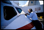 Mechanic leans across nose of TWA MD-80 changing windshield wiper motor; Lambert Airport/St. Louis Missouri