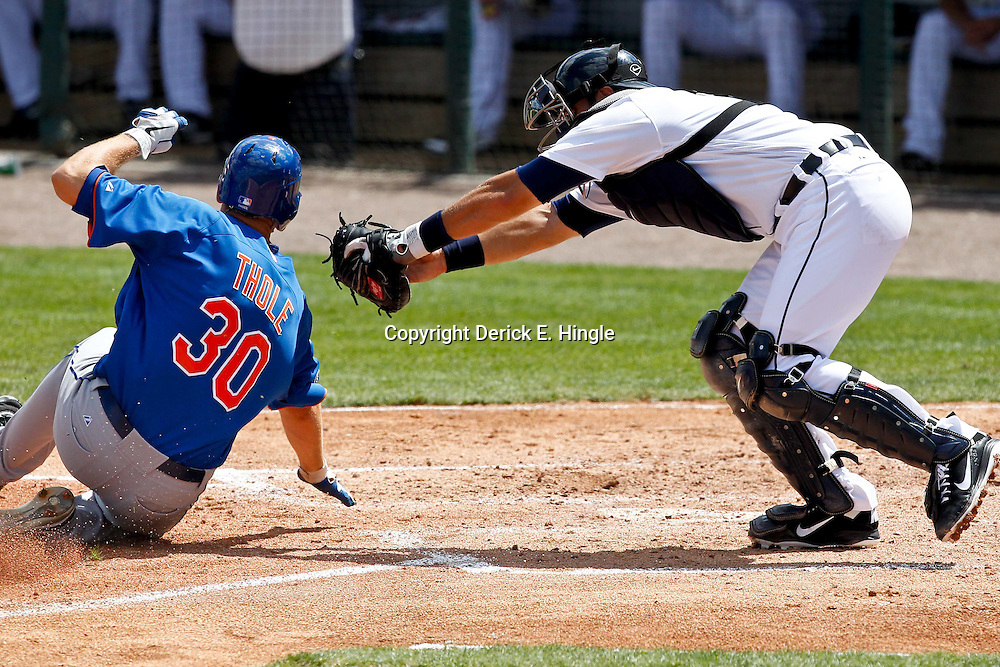March 14, 2012; Lakeland, FL, USA; New York Mets catcher Josh Thole (30) is tagged out at homeplate by Detroit Tigers catcher Alex Avila (13) to end the top of the third inning of a spring training game at Joker Marchant Stadium. Mandatory Credit: Derick E. Hingle-US PRESSWIRE