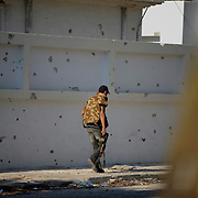 A rebel fighter passes by a partially destroyed wall in central Zawiya.