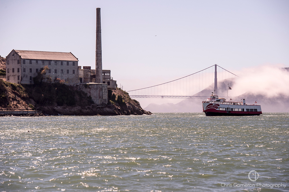 Red and White fleet ferry, Harbor Princess approaching Alcatraz with The Golden Gate Bridge in the back ground. San Francisco, California.