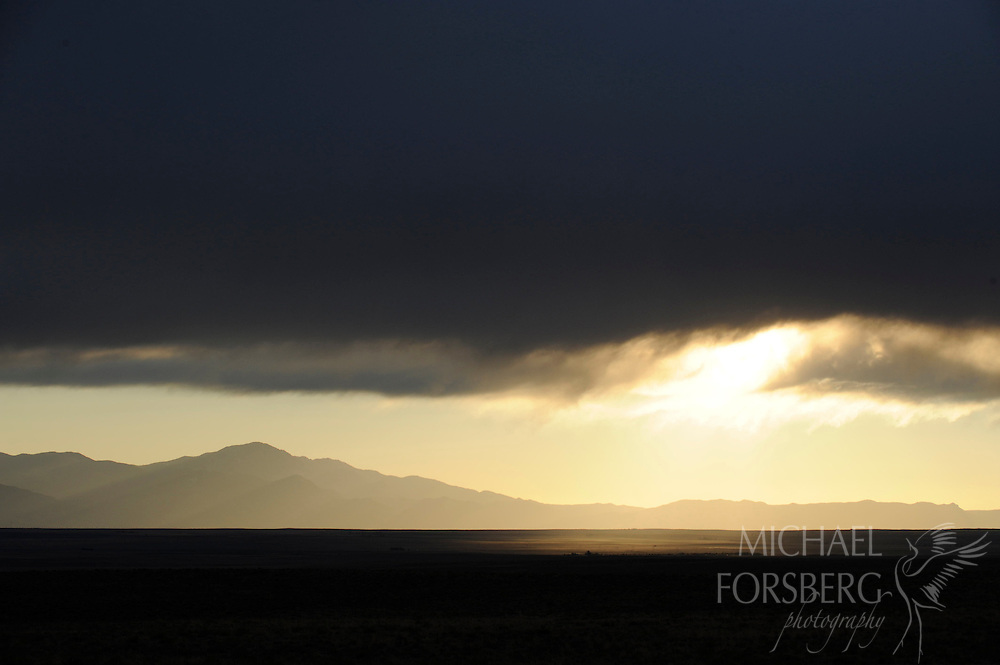 A shaft of sun highlights the shortgrass plains that roll east from Colorado's Front Range.  El Paso County, Colorado.