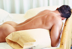 Naked young man lying on pillows on his bed