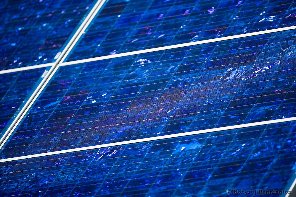 Electricity producing photovoltaic solar panels on a rooftop with blue sky