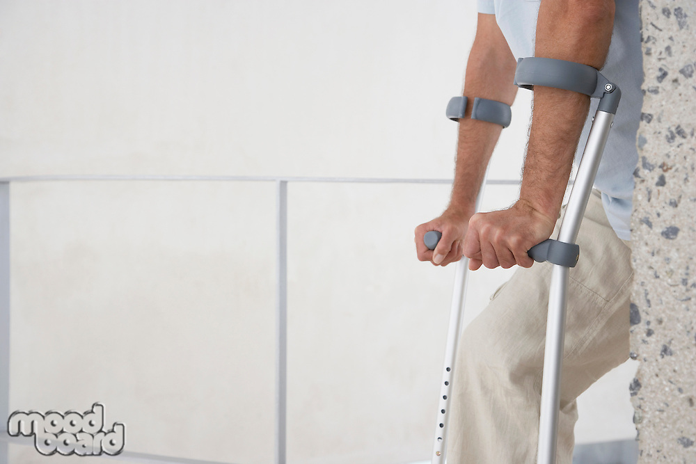 Mid-adult man on crutches mid section side view