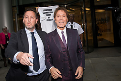 © Licensed to London News Pictures. 12/04/2018. London, UK. Sir Cliff Richard (right) leaves the Rolls Building at the Royal Courts of Justice, following the trial in legal battle between Sir Cliff Richard and the BBC. The performer is suing the BBC after it broadcast pictures and named Sir Cliff as a suspect in an alleged historical sexual assault. Photo credit : Tom Nicholson/LNP