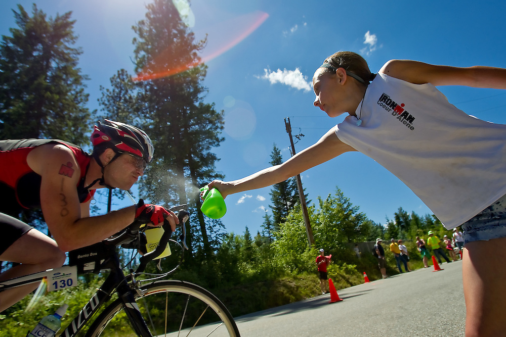Georgia Henkle, 10, spritzes Cameron Hjeltness, from Post Falls, with a water as he pedals along Dodd Road.
