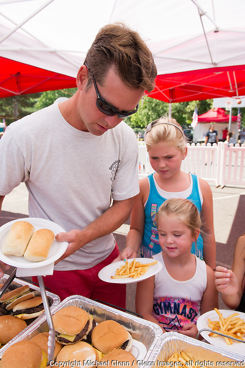 19 Sep 2015 Staten Island, New York US // Capt. Danny Keane helps his children get some food at the 8th annual Lt. John Martinson Memorial Picnic at the Hillside Swim Club //  Michael Glenn  /   for the FDNY