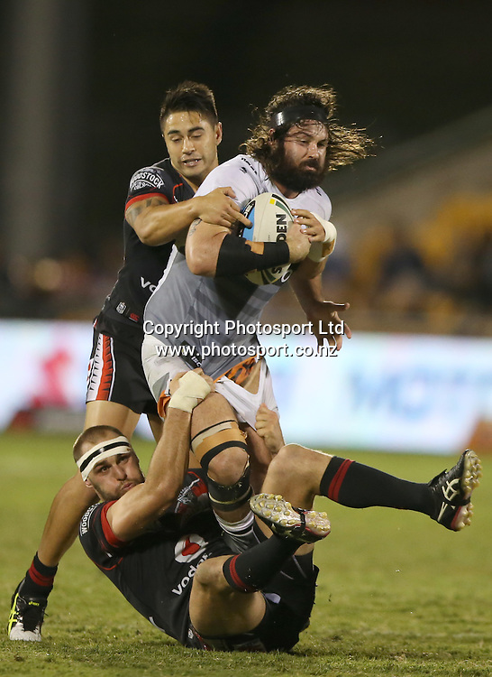 Warriors players Shaun Johnson, top, and Simon Mannering tackle Tigers player Aaron Woods during the NRL Rugby League Warriors vs Wests Tigers played at Mt Smart Stadium in Auckland New Zealand on 11 April 2015. <br /> <br /> Copyright Photo;  Peter Meecham/ www.photosport.co.nz