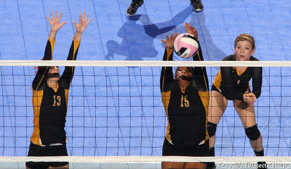 Janesville's Olivia Fisher (15) blocks the ball between Emily Ruth (13) and Erika Quistorff (1) during the second game of their 1A semifinal match in the state volleyball tournament at the U.S. Cellular Center at 370 1st Ave E on Friday evening, November 12, 2010. (Stephen Mally/Freelance)