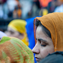 London, UK - 7 April 2013: a woman prays with her eyes closed during the Nagar Kirtan celebrations
