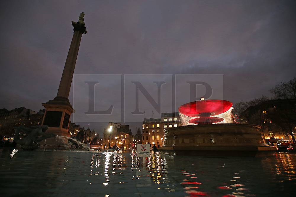 © Licensed to London News Pictures. 01/12/2015. London, UK. London's Trafalgar Square fountains are lit RED tonight to mark World AIDS Day. Every year, a number of buildings and monuments around the globe are illuminated RED on December 1 to raise awareness around the fight to end AIDS. Photo credit: Peter Macdiarmid/LNP
