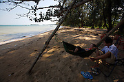 Phu Quoc Island. Bai Thom. Locals relaxing on the beach in the shadow of trees.