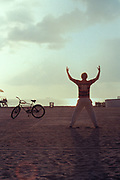 Man stretching on beach, evening, Miami, U.S.A, December, 2000.