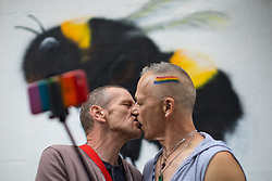 © Licensed to London News Pictures . 25/08/2017. Manchester , UK. Two men kiss as they take a selfie in front of a worker bee mural on Canal Street in Manchester's Gay Village on the opening night of Manchester Pride's Big Weekend . The annual festival , which is the largest of its type in Europe , celebrates LGBT life . Photo credit: Joel Goodman/LNP