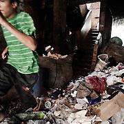 Un joven salta por encima de la basura almacenada en la planta baja de su casa en Mokattam. En medio del barrio de Manshiet Nasr a las afueras de El Cairo esta situado el asentamiento de Mokattam conocido como la &quot;Ciudad de la Basura&quot; , est&aacute; habitado por los Zabbaleen ,una comunidad de unos 45.000 cristianos coptos que viven desde hace varias d&eacute;cadas de reciclar los desperdicios que genera la capital egipcia: pl&aacute;stico, aluminio, papel y desechos &oacute;rganicos que transforman en compost . La mayor&iacute;a forman parte de la Asociaci&oacute;n para la Protecci&oacute;n del Ambiente (APE) una ONG que act&uacute;a en el &aacute;rea, cuyos objetivos son proteger el medio ambiente y aumentar el sustento de las recuperadores de basura de El Cairo. Seg&uacute;n la ONU, el trabajo que se realiza en Mokattam como uno de los diez mejores ejemplos del mundo en el mejoramiento medioambiental. El Cairo , Egipto, Junio 2011. ( Foto : Jordi Cam&iacute; )<br /> &laquo; less