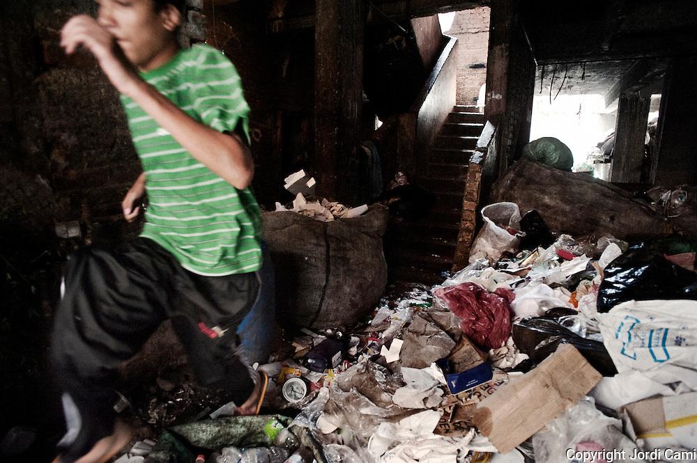 """Un joven salta por encima de la basura almacenada en la planta baja de su casa en Mokattam. En medio del barrio de Manshiet Nasr a las afueras de El Cairo esta situado el asentamiento de Mokattam conocido como la """"Ciudad de la Basura"""" , está habitado por los Zabbaleen ,una comunidad de unos 45.000 cristianos coptos que viven desde hace varias décadas de reciclar los desperdicios que genera la capital egipcia: plástico, aluminio, papel y desechos órganicos que transforman en compost . La mayoría forman parte de la Asociación para la Protección del Ambiente (APE) una ONG que actúa en el área, cuyos objetivos son proteger el medio ambiente y aumentar el sustento de las recuperadores de basura de El Cairo. Según la ONU, el trabajo que se realiza en Mokattam como uno de los diez mejores ejemplos del mundo en el mejoramiento medioambiental. El Cairo , Egipto, Junio 2011. ( Foto : Jordi Camí )<br /> « less"""