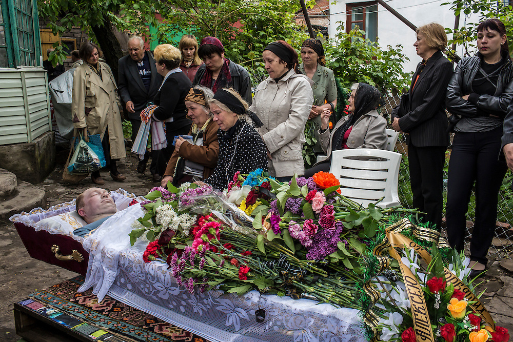 MARIUPOL, UKRAINE - MAY 12: Relatives of Alexey Vorobyov mourn over his body on May 12, 2014 in Mariupol, Ukraine. Vorobyov was a bystander when he was killed by a bullet during clashes at a local police station on May 9, with tensions heightened by the Victory Day holiday and a referendum on greater autonomy for the region arranged by pro-Russia activists. (Photo by Brendan Hoffman/Getty Images) *** Local Caption ***