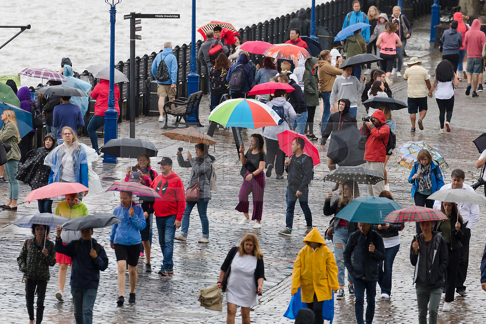 © Licensed to London News Pictures. 10/08/2018. London, UK.  Tourists during a heavy rain shower and wet weather near Tower Bridge at lunchtime today.  Photo credit: Vickie Flores/LNP