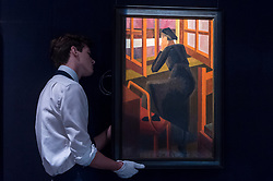 "© Licensed to London News Pictures. 16/11/2018. LONDON, UK. A technician hangs ""At the Window"", 1919, by David Bomberg (Est. GBP500,000-800,000). Preview of Sotheby's autumn sale of Modern & Post War British art.  Works from the British art scene of the past century will be offered for sale on 20 and 21 November 2018 at Sotheby's in London.  Photo credit: Stephen Chung/LNP"