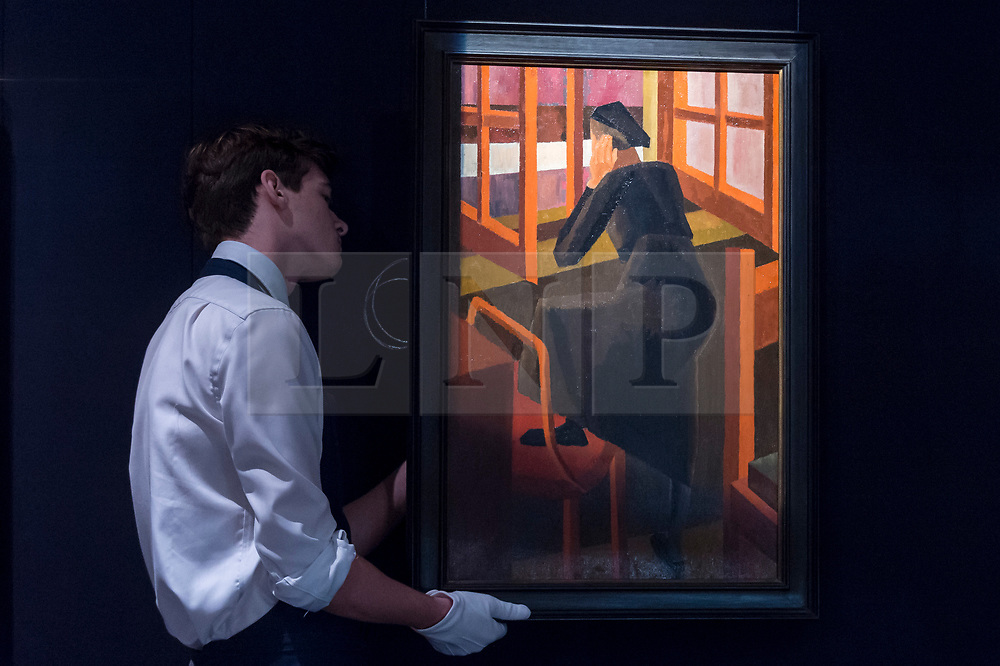 """© Licensed to London News Pictures. 16/11/2018. LONDON, UK. A technician hangs """"At the Window"""", 1919, by David Bomberg (Est. GBP500,000-800,000). Preview of Sotheby's autumn sale of Modern & Post War British art.  Works from the British art scene of the past century will be offered for sale on 20 and 21 November 2018 at Sotheby's in London.  Photo credit: Stephen Chung/LNP"""
