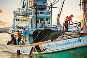 30 APRIL 2013 - MAHACHAI, SAMUT SAKHON, THAILAND:  Burmese crewman on a Thai fishing trawler coming back into port in Mahachai. The Thai fishing industry is heavily reliant on Burmese and Cambodian migrants. Burmese migrants crew many of the fishing boats that sail out of Samut Sakhon and staff many of the fish processing plants in Samut Sakhon, about 45 miles south of Bangkok. Migrants pay as much $700 (US) each to be smuggled from the Burmese border to Samut Sakhon for jobs that pay less than $5.00 (US) per day. There have also been reports that some Burmese workers are abused and held in slavery like conditions in the Thai fishing industry.          PHOTO BY JACK KURTZ