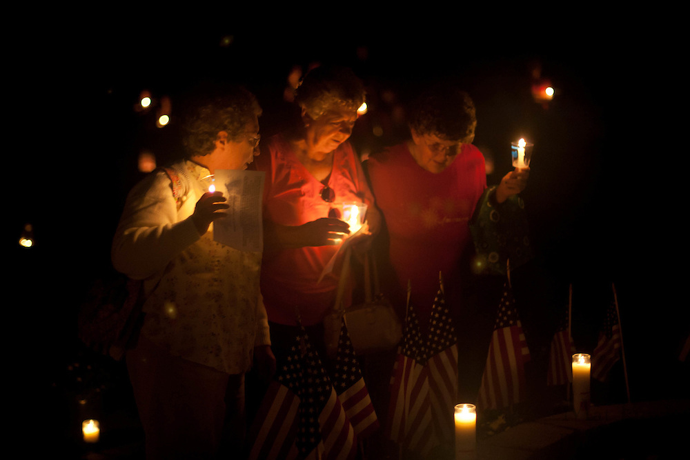 A group of women pause at the 9/11 memorial during a Candle Light Vigil held at Chestnut Branch Park in Mantua Saturday September 10.