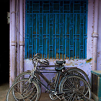 Many Bicycles Stacked Up Against A Blue Wall In Front Of A Mechanic Shop in Varanasi, India