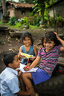 Matagalpa, Nicaragua, May 2014. two girls and a boy do their after school homework. We overnight at a homestay in La Corona village. The people own, or work in, small familiy coffee plantations that sell their Arabica coffee via Sol Cafe, a Fair Trade cooperative. Matagalpa tours offers trips to coffee plantations and remote villages, rural community tourism, agro-tourism, hiking and biking. Central America's largest and least populated country consists of lakes; volcanoes and Spanish colonial cities. Photo by Frits Meyst / MeystPhoto.com