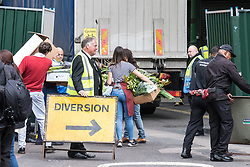 © Licensed to London News Pictures. 12/06/2017. London, UK. Flowers are carried in to Borough Market as traders begin clearing up and prepare to reopen. The market was the scene of a terrorist attack on Saturday 3 June 2017 in which eight people were killed. Photo credit: Rob Pinney/LNP