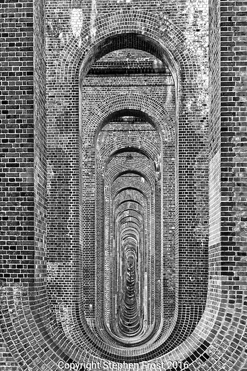 The tunnel through the brick supports of the Ouse Valley Viaduct (also called Balcombe Viaduct)  built in 1841, on the London to Brighton Railway Line in West Sussex,, England and 1,475 feet (450 m) long.<br />