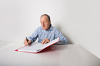 Senior businessman writing in file at desk