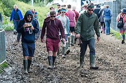 © Licensed to London News Pictures. 13/06/2015. Isle of Wight, UK.  Festival goers battle through muddy conditions, eyes down, at Isle of Wight Festival 2015 on the morning of Saturday Day 3.  Yesterday suffered torrential rain all afternoon and evening, after a first day of warm sun.  This years festival include headline artists the Prodigy, Blur and Fleetwood Mac.  Photo credit : Richard Isaac/LNP