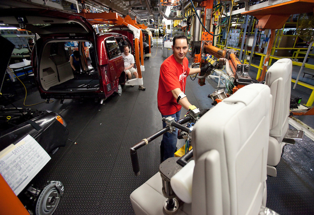 A worker on the production line at Chrysler's plant in Windsor, Ontario,  installs the seats in one of the company's new minivans during the production launch of the new Dodge Grand Caravan and Chrysler Town and Country,  January 18, 2011.<br /> The Canadian Press/GEOFF ROBINS
