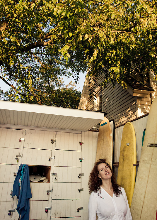 Veronica, a local femaile surfer, stands near her her locker at Boarders Surf Shop in Rockaway Beach, Queens, NY.