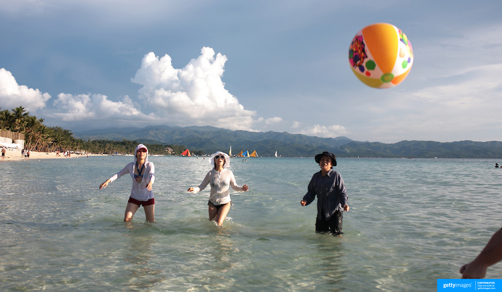 Asian tourists playing a ball game in the pristine waters of White Beach,  Boracay Island, the Philippines on October 3, 2008, Photo Tim Clayton..Asian tourists at White Beach, Boracay Island, the Philippines...The 4 km stretch of White beach on Boracay Island, the Philippines has been honoured as the best leisure destination in Asia beating popular destinations such as Bali in Indonesia and Sanya in China in a recent survey conducted by an International Travel Magazine with 2.2 million viewers taking part in the online poll...Last year, close to 600,000 visitors visited Boracay with South Korea providing 128,909 visitors followed by Japan, 35,294, USA, 13,362 and China 12,720...A popular destination for South Korean divers and honeymooners, Boracay is now attracting crowds of tourists from mainland China who are arriving in ever increasing numbers. In Asia, China has already overtaken Japan to become the largest source of outland travelers...Boracay's main attraction is 4 km of pristine powder fine white sand and the crystal clear azure water making it a popular destination for Scuba diving with nearly 20 dive centers along White beach. The stretch of shady palm trees separate the beach from the line of hotels, restaurants, bars and cafes. It's pulsating nightlife with the friendly locals make it increasingly popular with the asian tourists...The Boracay sailing boats provide endless tourist entertainment, particularly during the amazing sunsets when the silhouetted sails provide picture postcard scenes along the shoreline...Boracay Island is situated an hours flight from Manila and it's close proximity to South Korea, China, Taiwan and Japan means it is a growing destination for Asian tourists... By 2010, the island of Boracay expects to have 1,000,000 visitors.