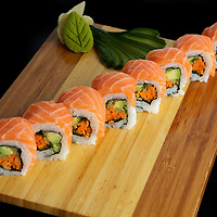 Rolls of sush on a wooden trayi over black background