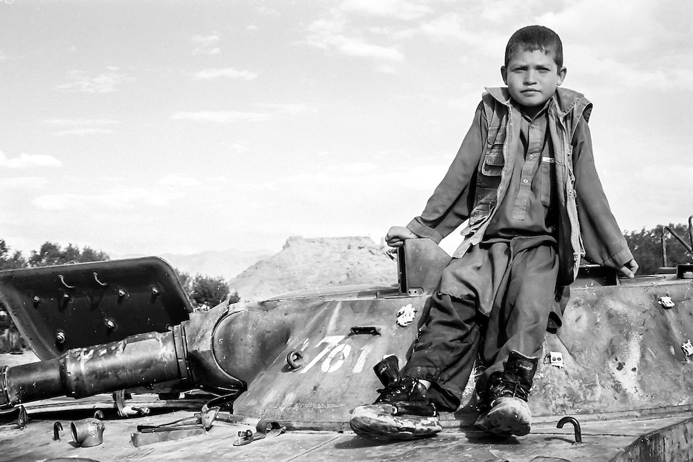 Young Afghan hazara boy sitting on an abandoned tank at the tank cemetery of Bamiyan (Afghanistan, 2005).